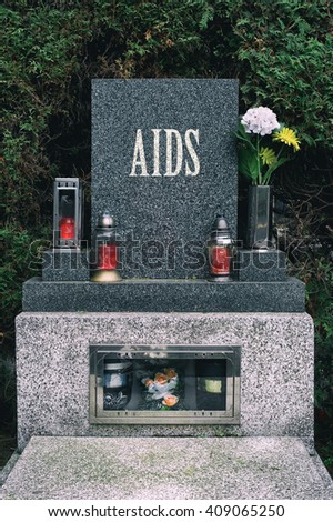 AIDS as civilization disease. Gravestone with text AIDS. Metaphor of victims who died or disease eradication by progress in medicine. (effect: muted blacks) - stock photo