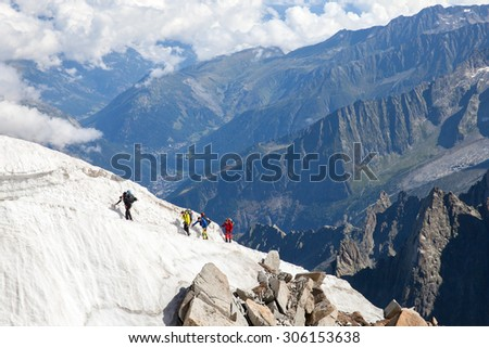 AIGUILLE DU MIDI, FRANCE - JUL 23, 2015: Four alpinists ascend on snow patch near from white valley in French Alps