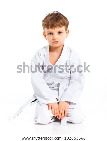 Aikido boy recreation position in white kimono isolated on white - stock photo