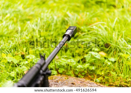 Aiming a rifle in the grass after the morning rain. Close up view from ground level, focus on the flame arrestor