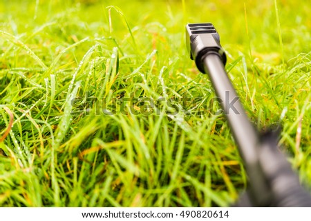 Aiming a rifle in the grass covered with morning dew. Close up view from ground level, focus on the flame arrestor