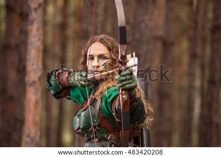 Aiming Elf woman in green leather armor with the bow and arrows is hunting on the forest background.