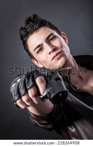 Aiming. Serious man with a gun on a black background - stock photo