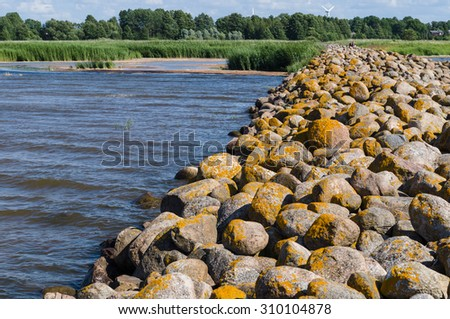 Ainazi North pier stones covered by yellow moss and backwater view, Latvia