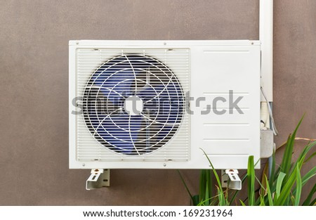 Air compressor on brown wall - stock photo