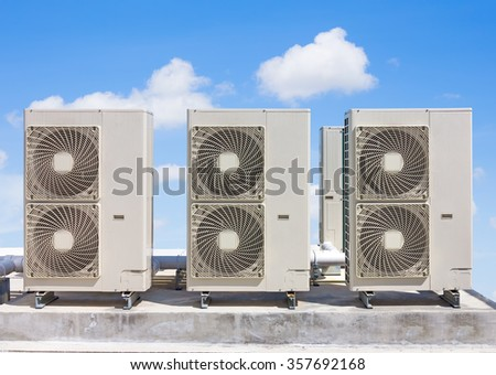Air compressor on concrete pedestal  with blue sky background. - stock photo