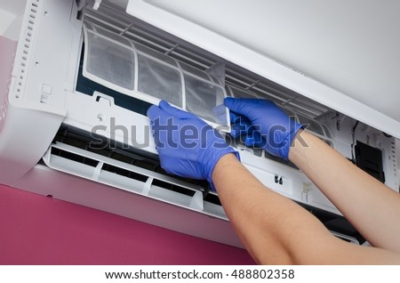Air conditioner cleaning. Man in gloves checks the filter.