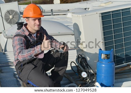 Air Conditioner Repairman Thumbs up, repairman working on a compressor and giving a thumbs up. Model is actual electrician. - stock photo