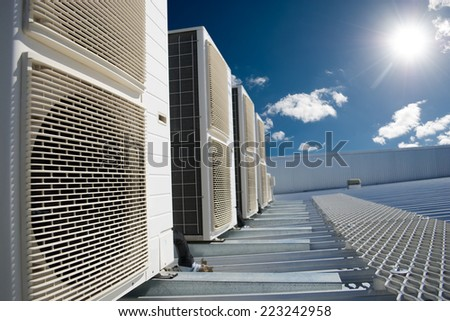Air conditioner units on a roof of industrial building with blue sky and clouds in the background. - stock photo