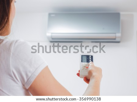 Air Conditioner , woman hand with remote control, adjustment temperature,at home - stock photo