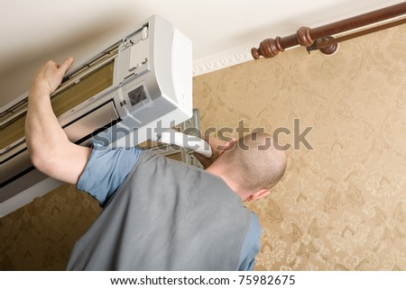 Air conditioning master installs a new air conditioner in the apartment. - stock photo