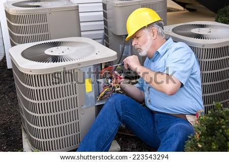 Air Conditioning Repairman At Work/ Horizontal Shot - stock photo