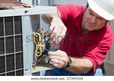 Air conditioning repairman rewiring a compressor unit.  Focus on the man's hands and the wires. - stock photo