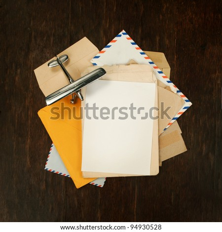 air cover and envelopes with model airplane as background square - stock photo
