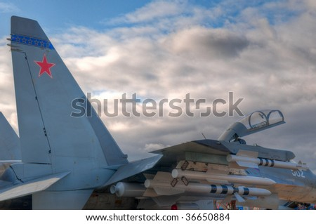 air fighter on the ground with opened cockpit, fully armed with missles with blue sky in background