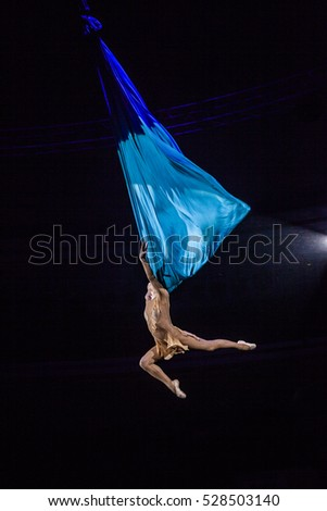 Air gymnast on cloths. Rhapsody of Love. Circus artist. Flying under the big top.