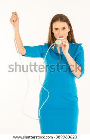 Air hostess in blue uniform. She explains how to use an oxygen mask in emergency case - stock photo
