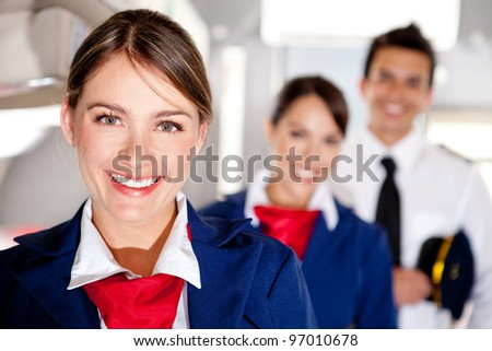 Air hostess with the airplane cabin crew smiling - stock photo