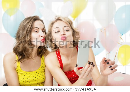 Air kiss. Selfie,  video call over the Internet. Two beautiful woman playful having fun. Pijamas party cool active mood festive atmosphere - stock photo
