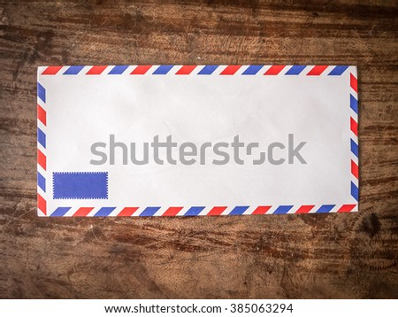 Air mail letter on wood background.