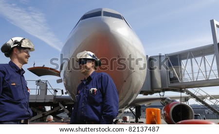 air mechanics with large airliner in background, passenger-bridge showing - stock photo