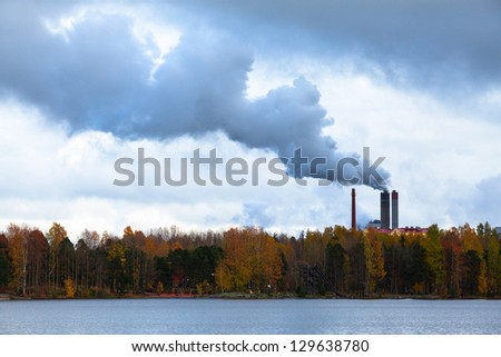 Air pollution by smoke coming out of three factory chimneys - stock photo