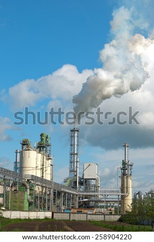 Air pollution by smoke coming out of two factory chimneys.  - stock photo