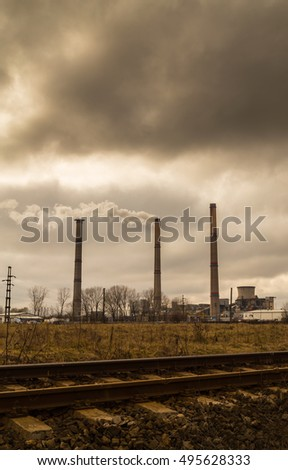 Air pollution from coal-powered plant smoke stacks, and industrial cityscape along railroad track, on a gloomy, overcast day