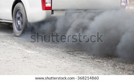 Air pollution from vehicle exhaust pipe on road - stock photo