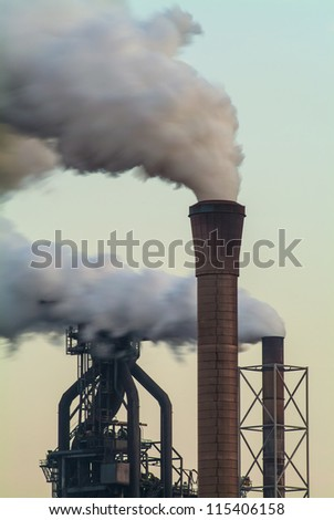 Air pollution of a factory with several chimneys in the evening - stock photo