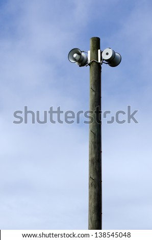 Air raid siren against blue sky. - stock photo