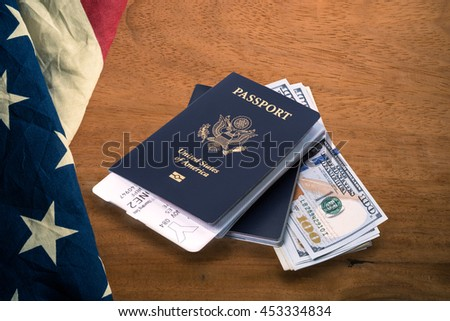 Air ticket in US passport on 100 US dollar bill with United State of America flag background, concept for travel time - stock photo