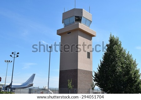 air traffic control tower with jet tail - stock photo
