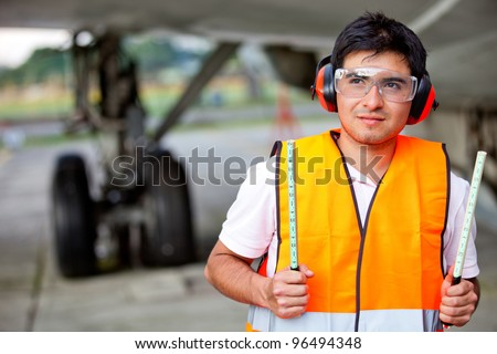 Air traffic controller holding light signs at the airport - stock photo