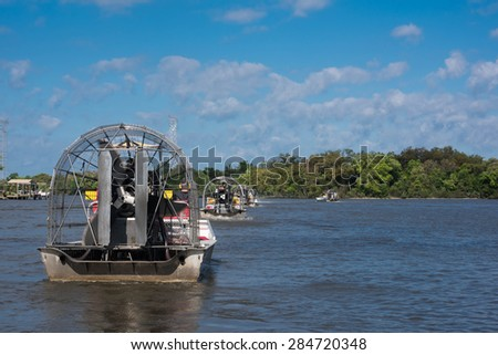 Airboats with tourists leaving on guided tour through Louisiana swamps - stock photo