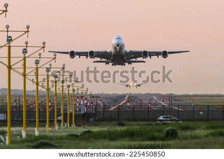 Airbus A380 airliner taking off while second jet lands in background - stock photo