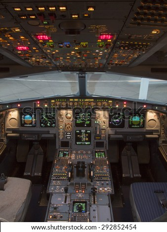 Airbus A330 airplane's cockpit with front,overhead and pedestrian panel taken on ground at dusk with concrete pavement in background.  - stock photo