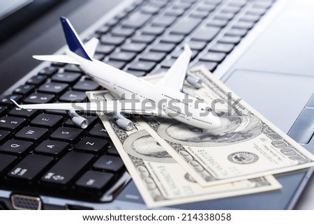 Aircraft and banknotes above laptop - stock photo