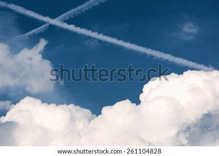 Aircraft contrails crossing and forming an X in a blue sky - stock photo