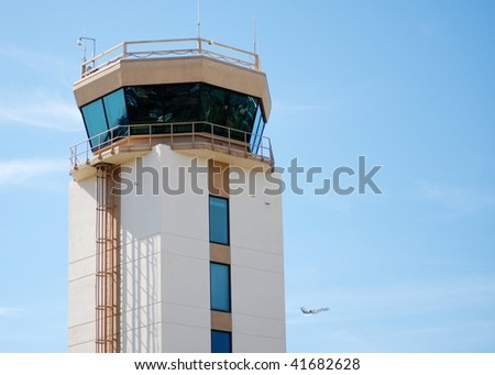 Aircraft control tower on sunny day. The tower is large with windows all around.  There are a few high clouds and a distant airplane is taking off lower right. Horizontal composition leave copy space - stock photo