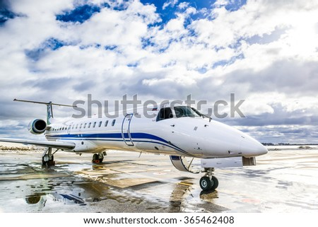 Aircraft Embraer ERJ 145 on the runway.  SYKTYVKAR, RUSSIA - MARCH 12, 2015: Parked aircraft Embraer ERJ 145 be inspected before the scheduled flight to the neighboring cities. - stock photo
