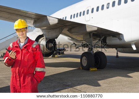 Aircraft engineer with CB radio standing in front of a commercial airliner - stock photo