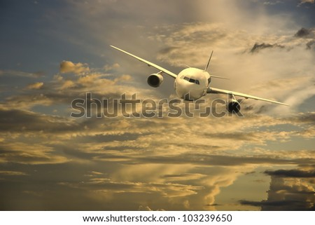 Aircraft flying in the sky at sunset - stock photo