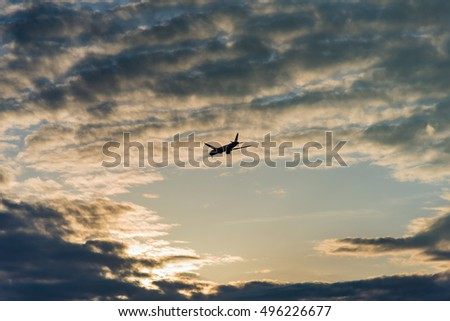 aircraft flying in the sky storm clouds sunset