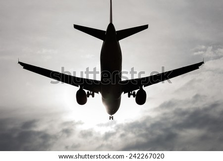 aircraft flying over a sky with clouds backlit - stock photo