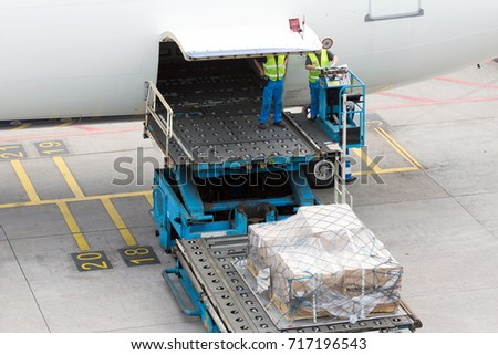 Aircraft handling before flight. Technician staff load the cargo pallets in the airplane cargo compartment.