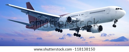 Aircraft is maneuvering in a sunset sky. Panoramic composition. - stock photo
