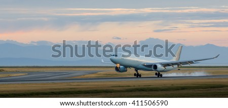 Aircraft landing at YVR at dusk with mountains in the background. - stock photo
