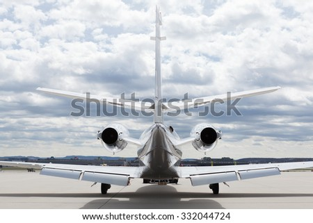 Aircraft learjet Plane in front of the Airport with cloudy sky and sun