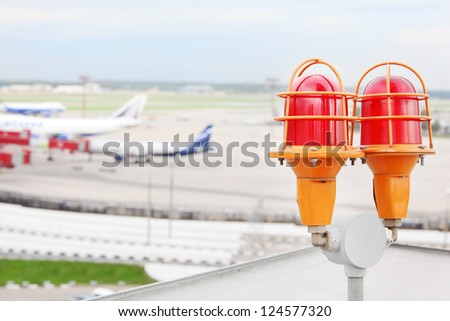 Aircraft lights at roof of building against background of passenger aircrafts in airport. - stock photo